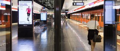 kuva metroaseman digitaalisesta ulkomainoksesta ja ihminen oranssi metro